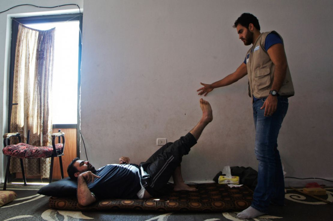A victim of the Syrian conflict, supported by an HI specialist, is doing physiotherapy exercises