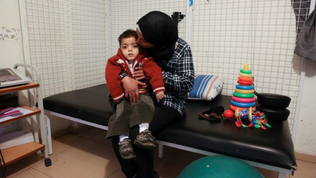 Abdel Kareem, 5, with his mother at the Mousawat rehabilitation centre; }}