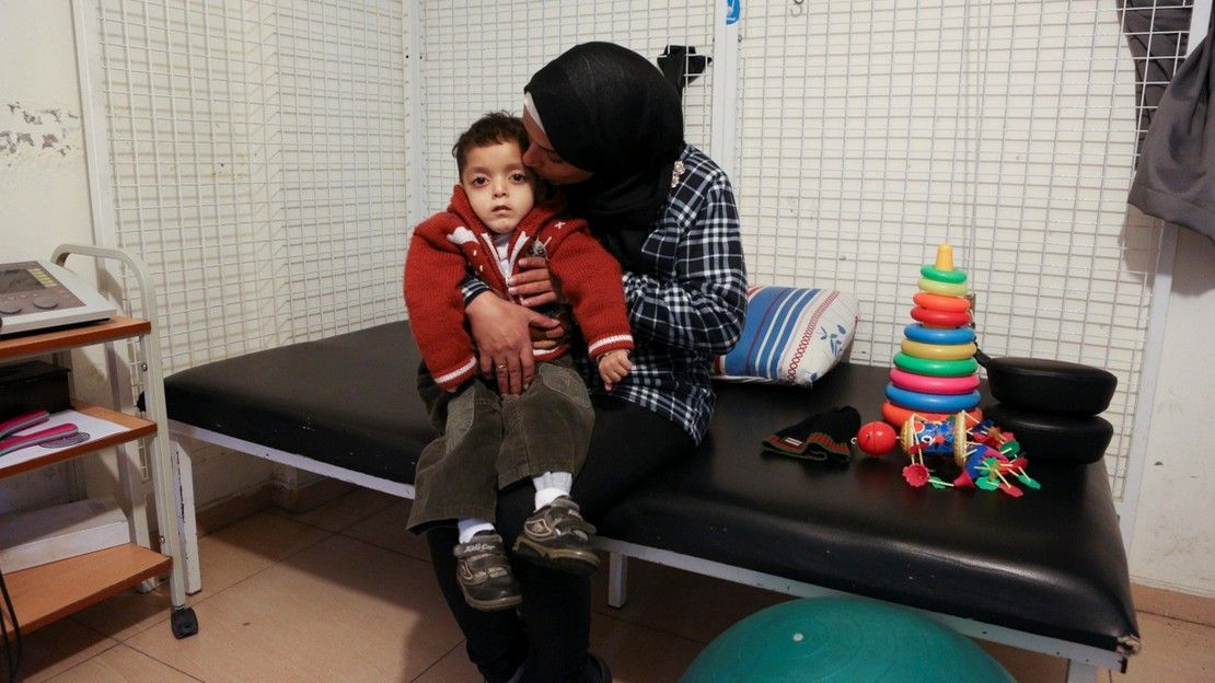 Abdel Kareem, 5, with his mother at the Mousawat rehabilitation centre